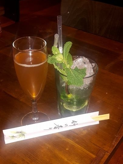 Two cocktails on a table next to chopsticks